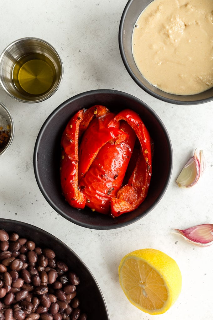 Roasted red peppers in a black bowl and next to other ingredients.