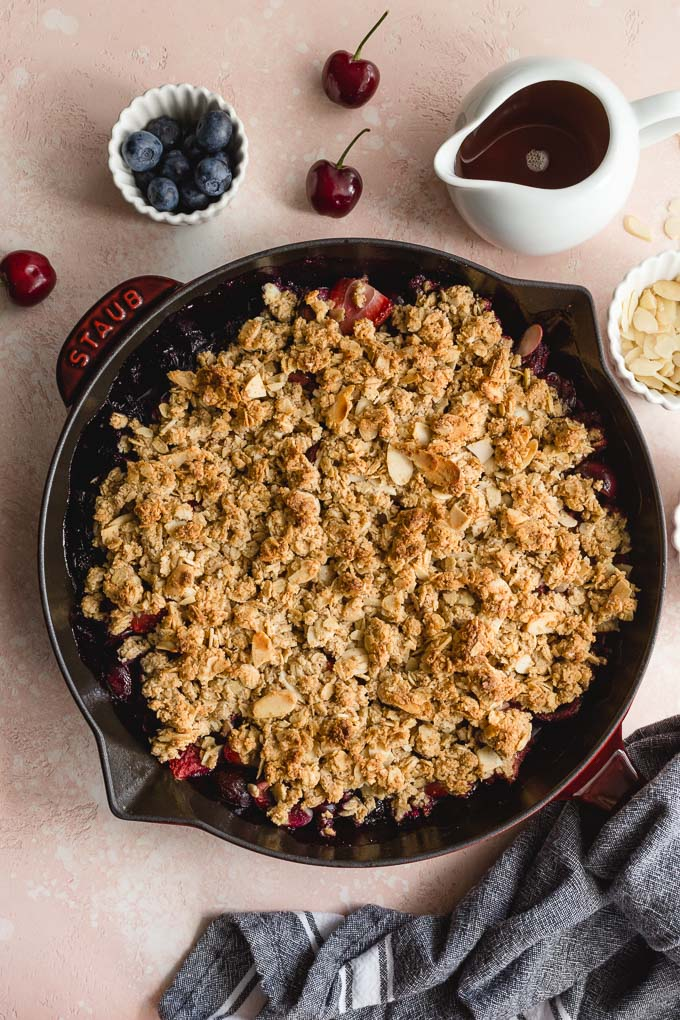 Healthy cherry crisp baked up in a cast iron skillet and resting on a pink surface.