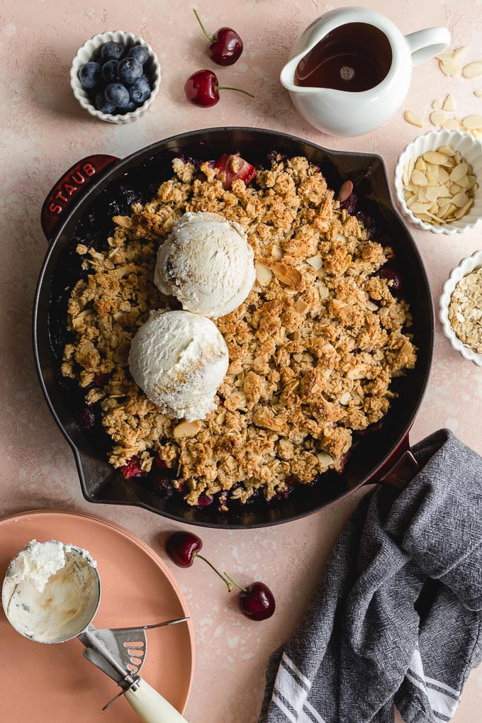 Overhead view of a cherry almond crisp in a cast iron pan with scoops of ice cream on top.