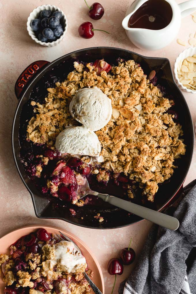 Fresh cherry crisp in a skillet being scooped onto pink plates.