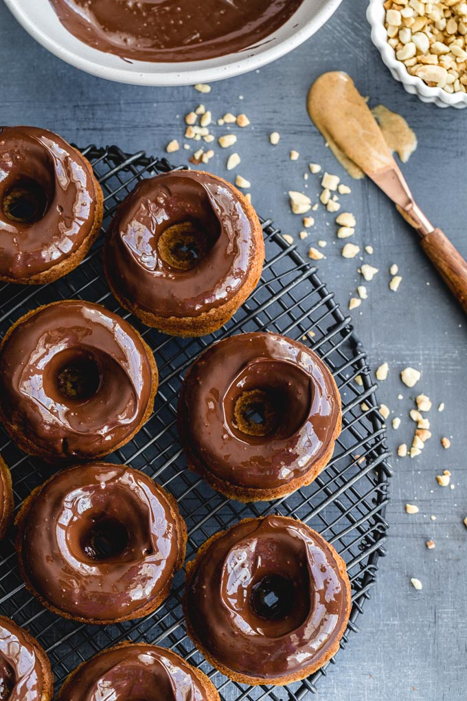 Pronuts with chocolate peanut butter glaze on a wire rack.