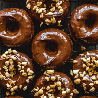Protein donuts topped with chocolate peanut butter glaze and chopped peanuts.