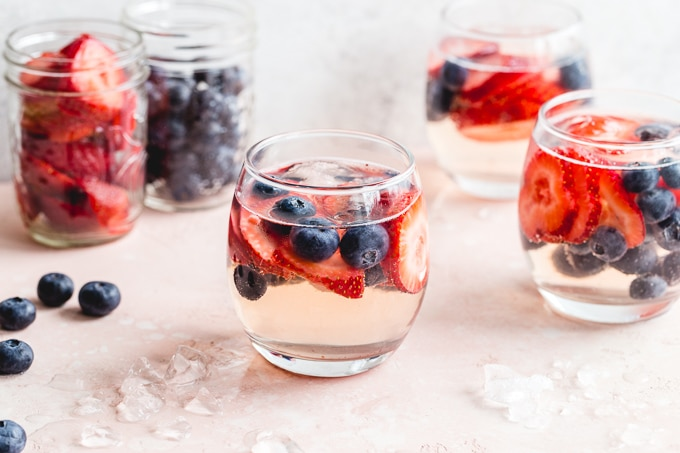Side view of wine spritzers in wine glasses with berries.