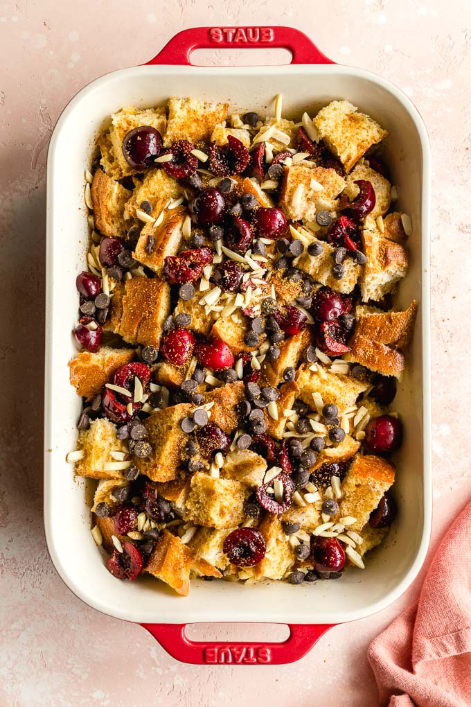 French toast bake assembled in a red baking dish and ready for the oven.