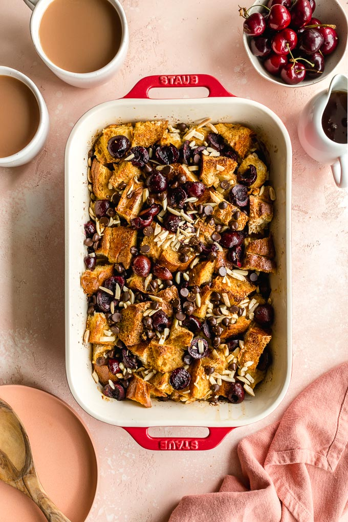 Overhead view of baked french toast with cherries in a rectangular baking dish on a pink surface.