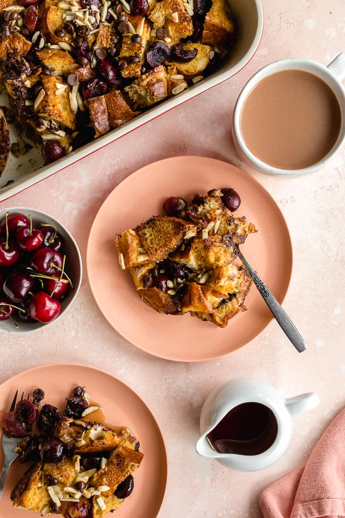 Cherry french toast casserole served on pink plates next to the baking dish.