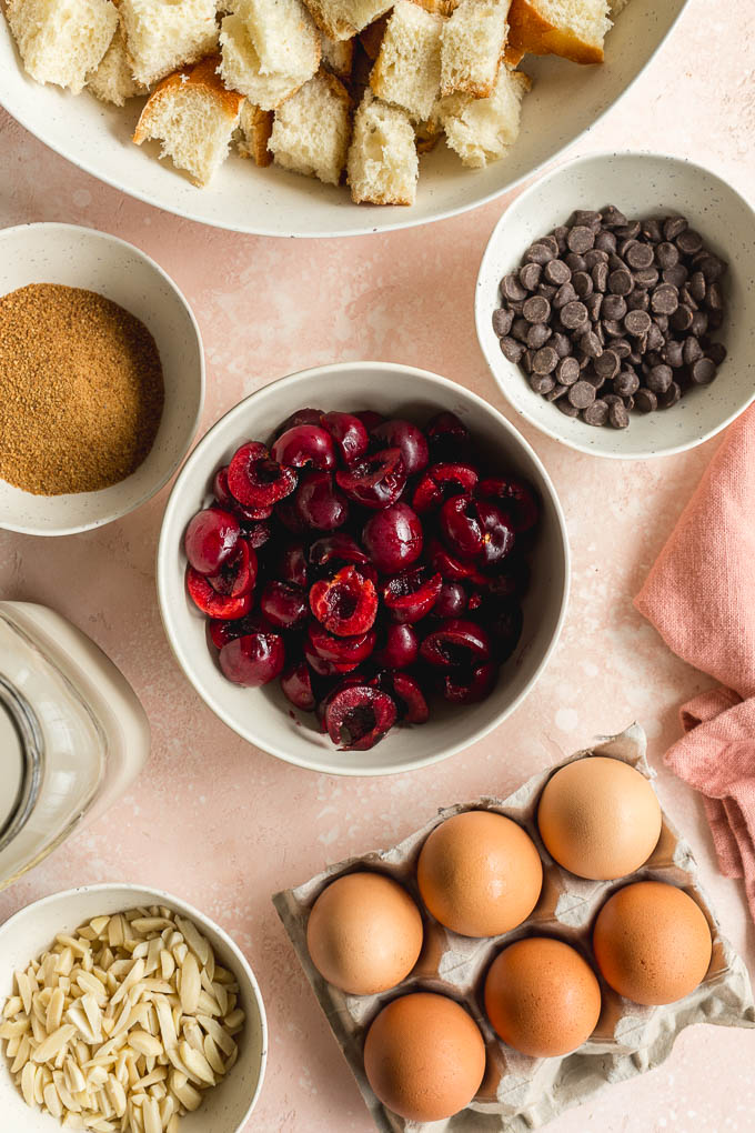 Ingredients to make cherry french toast casserole arranged on a pink surface.