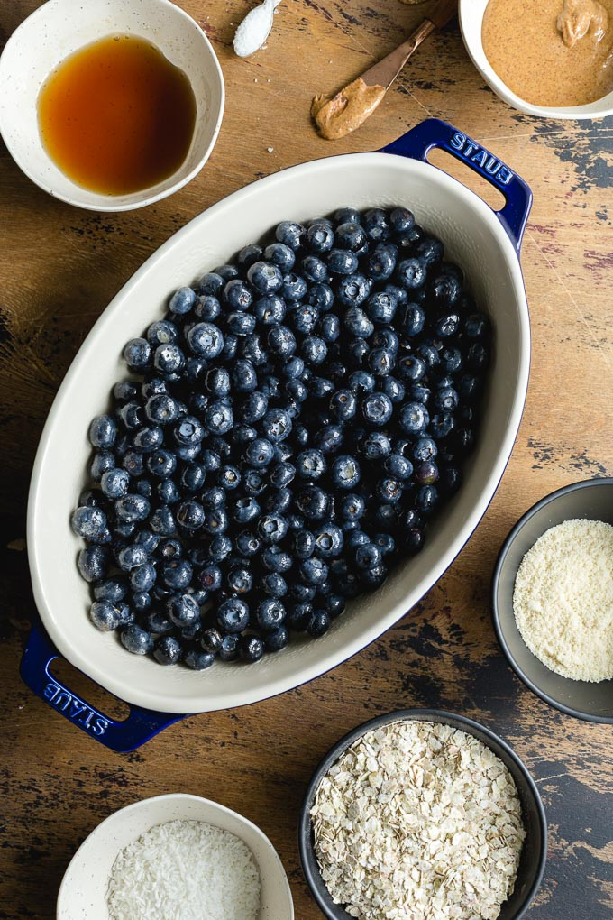 Fresh blueberries in a baking dish surrounded by other crisp ingredients.