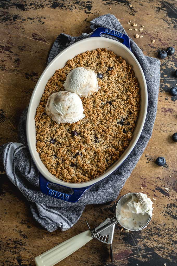 Vegan blueberry crisp in a blue dish and topped with dairy-free ice cream.