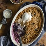 Healthy blueberry crisp baked up in a blue dish and topped with ice cream.