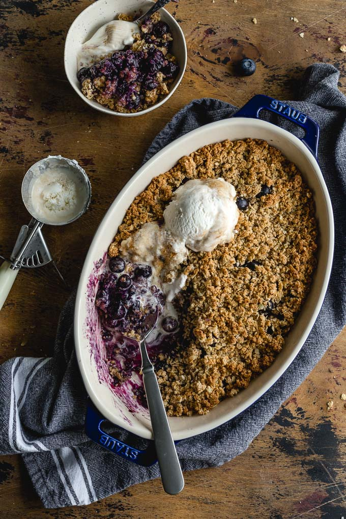 Overhead view of a blueberry crisp in a baking dish and topped with ice cream.