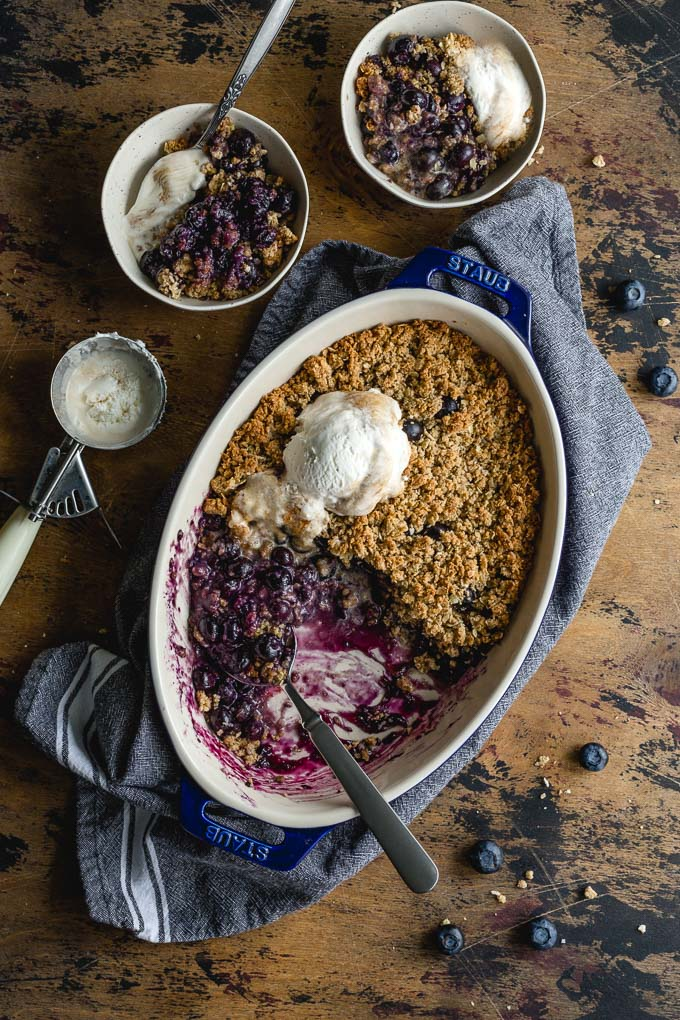 Overhead view of a blueberry crisp in a baking dish, with portions scooped out into little bowls.