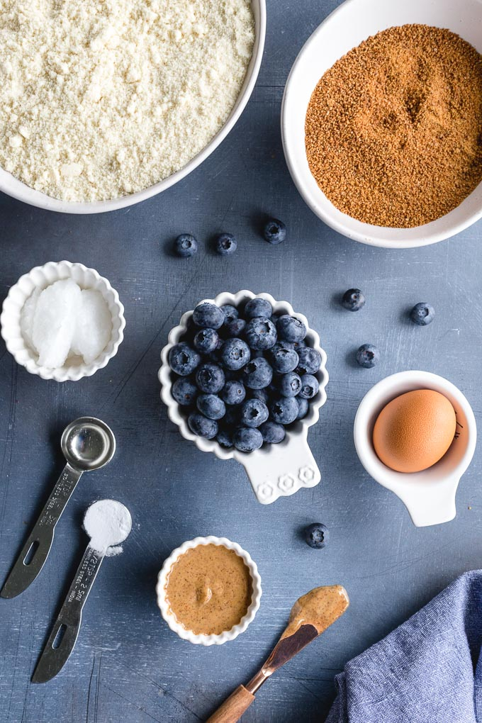 Ingredients to make an almond flour skillet cookie with blueberries arranged individually on a blue surface.