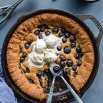 Overhead view of a blueberry skillet cookie topped with ice cream and two spoons inserted into it.