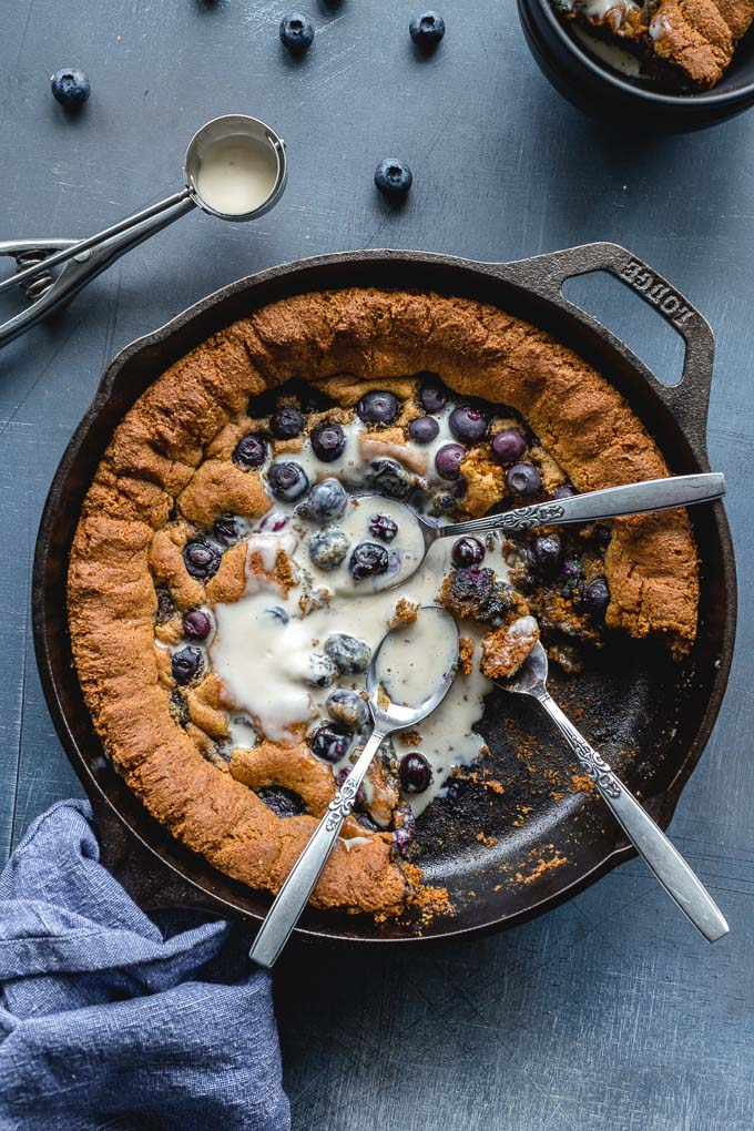 Overhead view of a giant blueberry cookie in a skillet with melted ice cream.