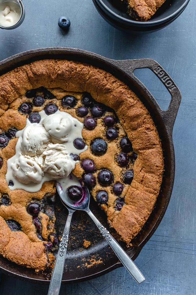 Up-close view of a skillet cookie with blueberries and ice cream.