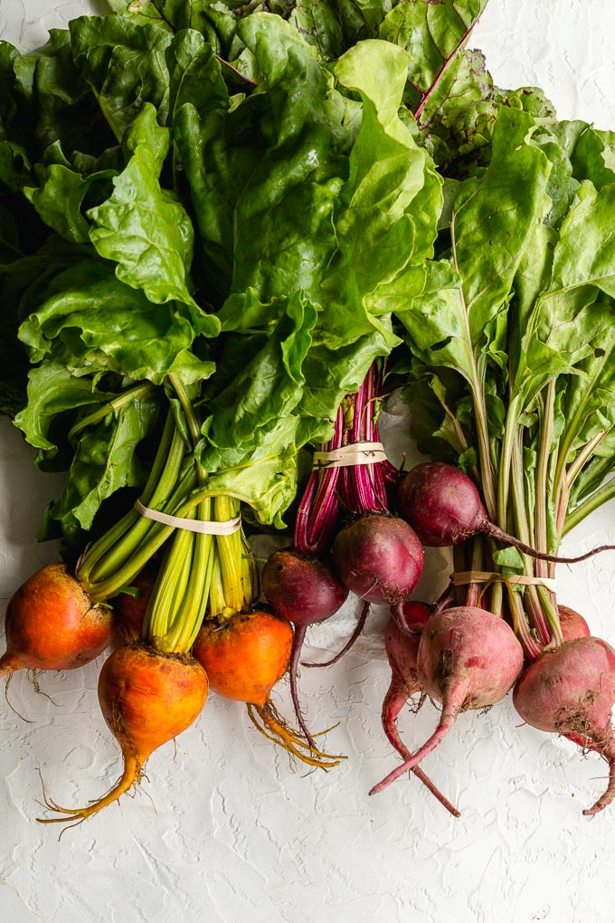 Three different varieties of beet bunches arranged on a white surface - red beets, golden beets and candy cane beets.