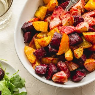 Up close view of air fryer roasted beets in a white bowl with a spoon inserted into the beets.