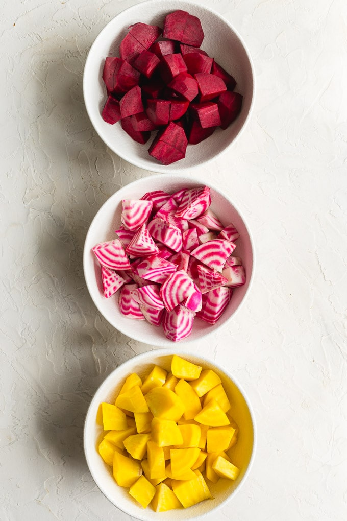 Red beets, golden beets and Chioggia beets cut into pieces and arranged in individuals white bowls.