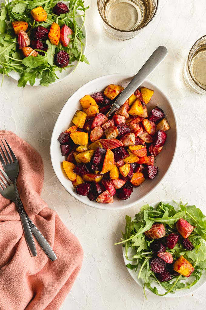 Overhead view of air fryer roasted beets in a white bowl with plates of arugula and beets off to the sides.