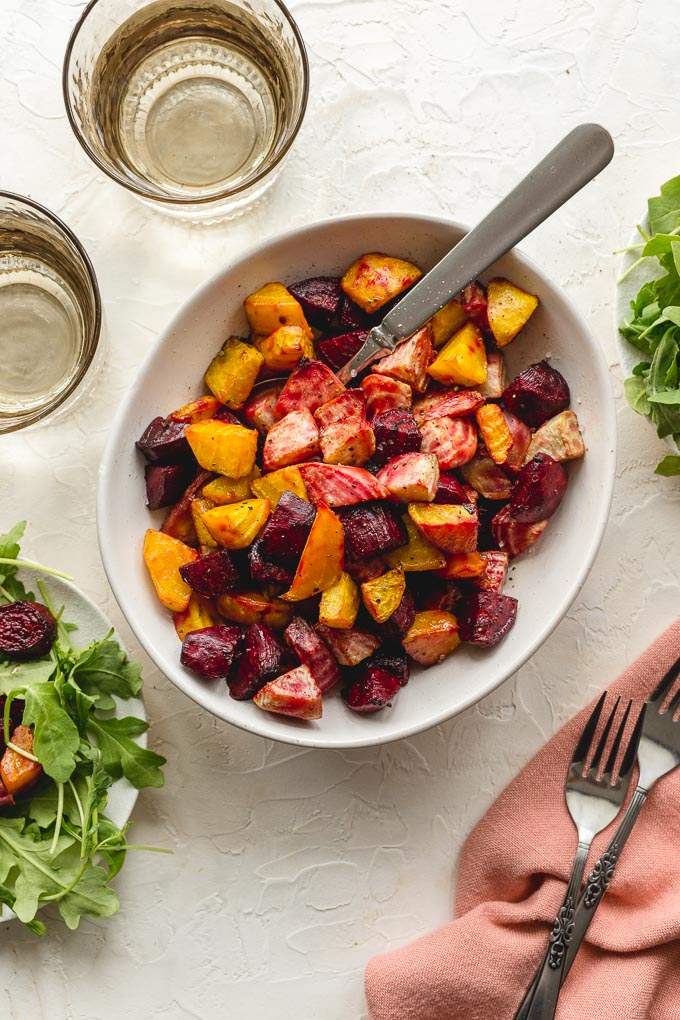 Air fried beets in a white bowl with a spoon and glasses of water off to the side.