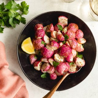 Overhead view of air fryer radishes in a black bowl on a white surface with lemon and parsley on the side.