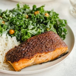 Up close view of a piece of air fryer salmon plated with a green salad and rice.