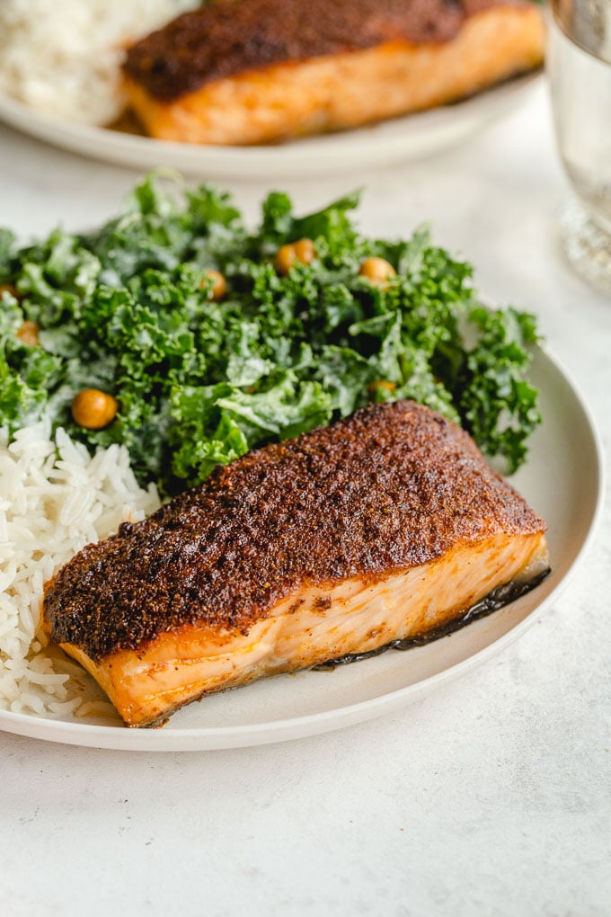 Side view of a crispy air fried salmon fillet on a plate with rice and kale.
