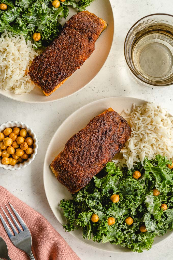 Overhead view of air fryer salmon fillets on two plates along with kale and rice.