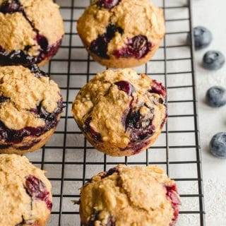 Healthy Blueberry Oatmeal Muffins cooling on a black wire rack.