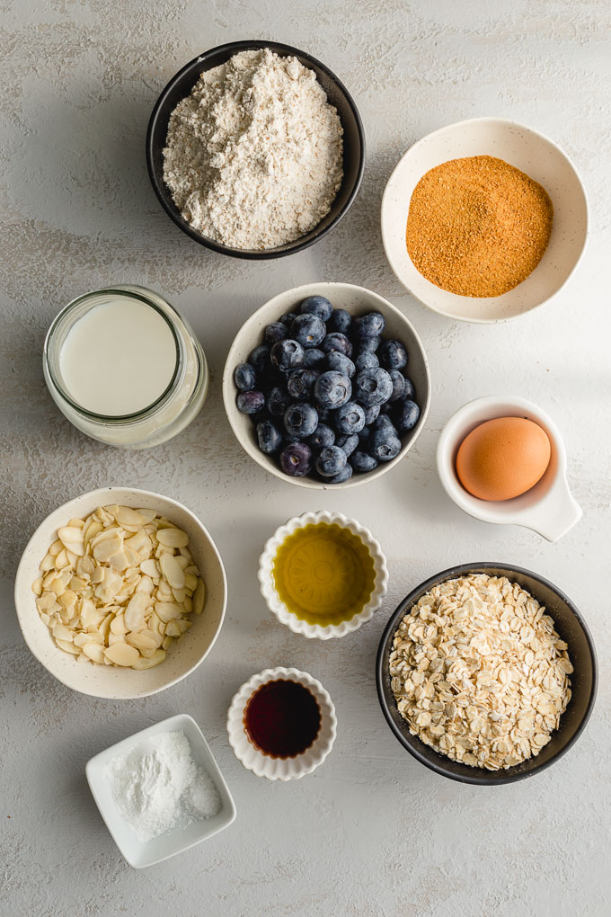 Ingredients to make dairy-free blueberry muffins arranged in individual bowls.