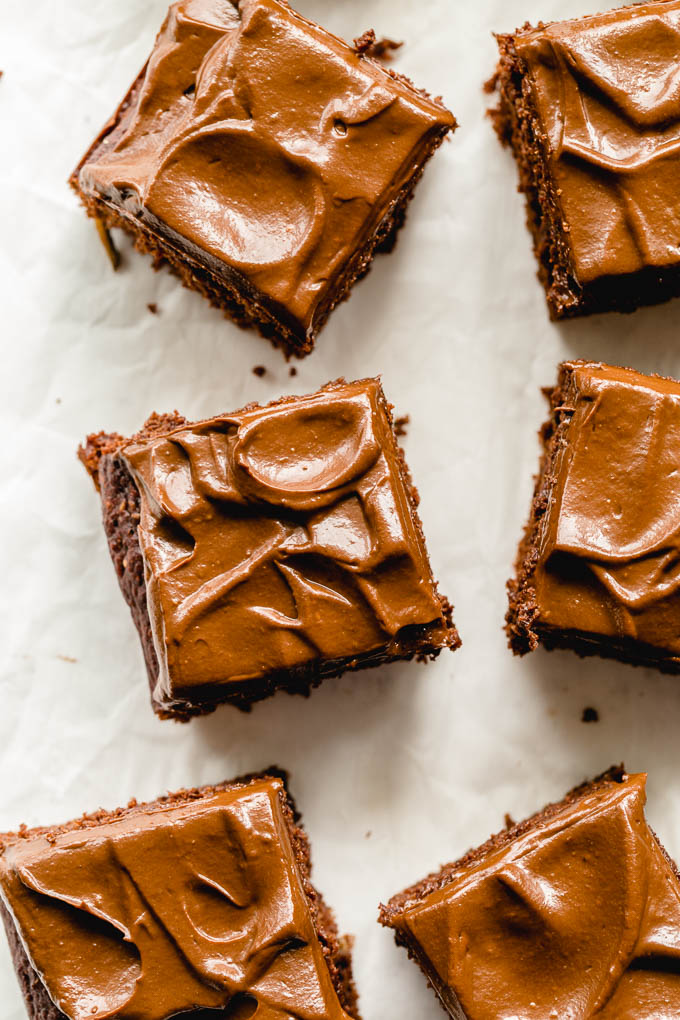 Up close view of zucchini cake topped with chocolate frosting and cut into squares.
