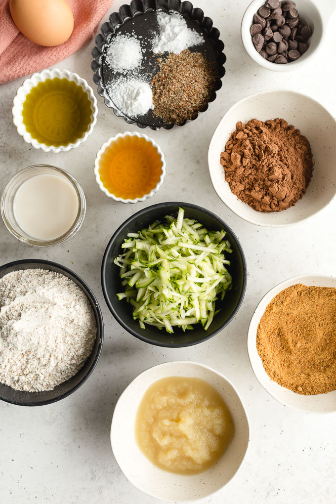 Overhead view of ingredients to make healthy chocolate zucchini cake arranged in individual bowls.