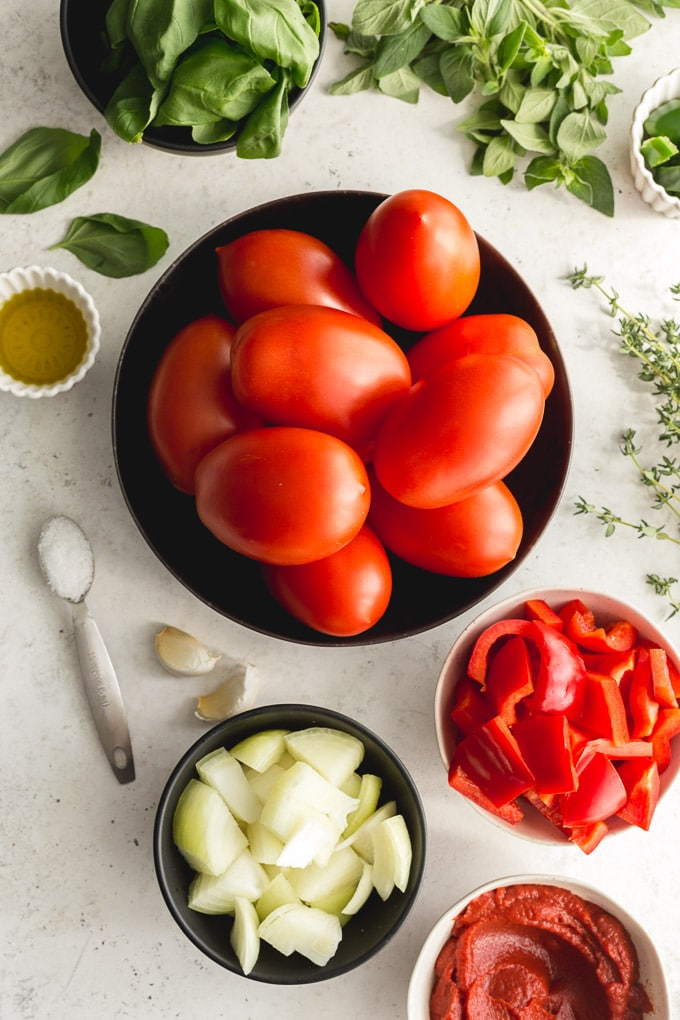 Plum tomatoes and other marinara sauce ingredients arranged in individual bowls.