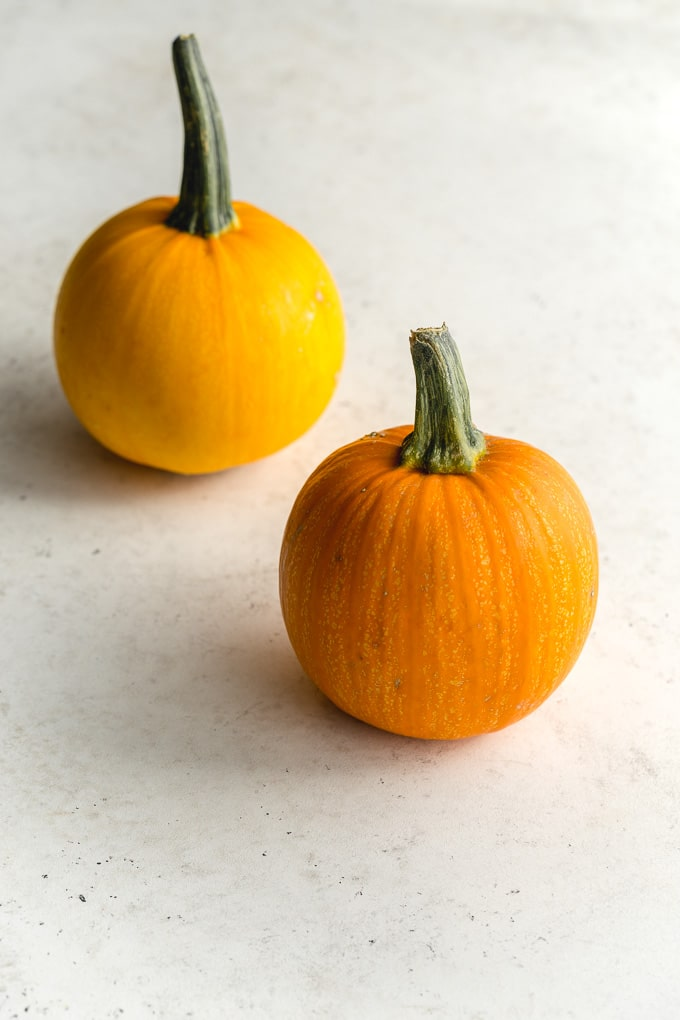 Two small Jack Be Little pumpkins arranged on a light coloured surface.