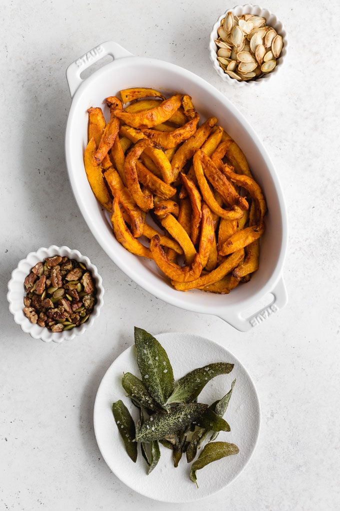 Overhead view of roasted pumpkin fries in a white dish with granola, pumpkin seeds and crispy sage off to the sides.
