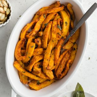 Up close and overhead view of air fryer pumpkin fries in a white dish with a fork inserted into it.