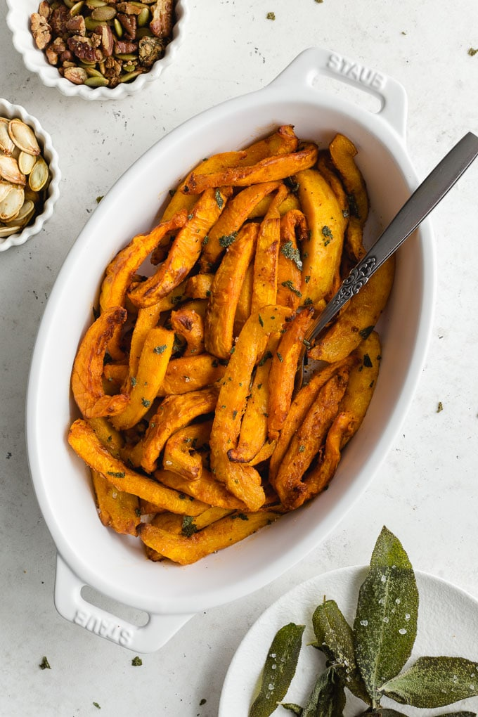 Overhead view of air fryer pumpkin fries in a white oval dish.