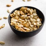 Air fryer pumpkin seeds in a small black bowl with seeds scattered around it.