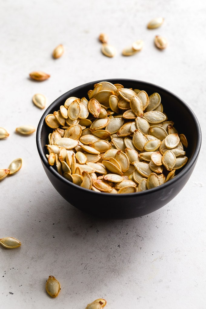 Toasted pumpkin seeds in a black bowl on a light coloured surface.