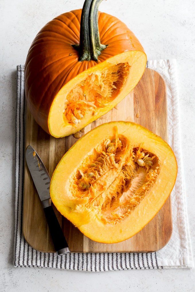 Overhead image of a large pumpkin cut in half on a wooden cutting board, with the seeds and flesh exposed.