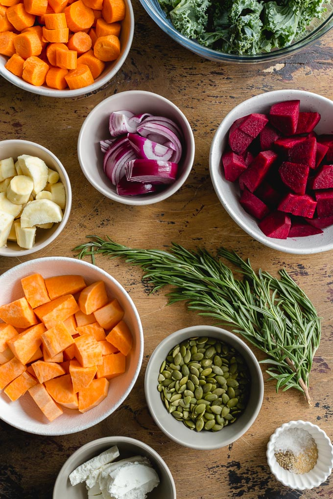 Ingredients to make a root vegetable salad with kale arranged in individual bowls on a wooden surface.