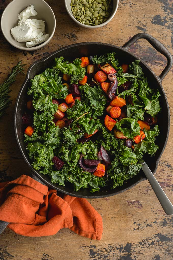 Roasted vegetables in a cast iron skillet with wilted kale and pumpkin and goat cheese off to the side.