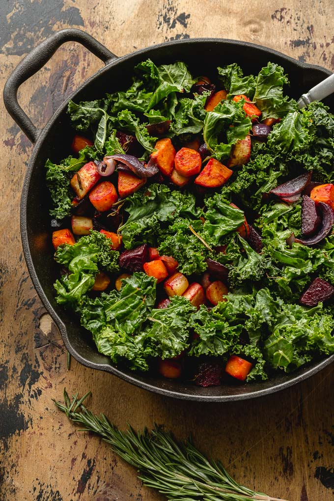 Up close view of roasted veggies and kale in a cast iron skillet.