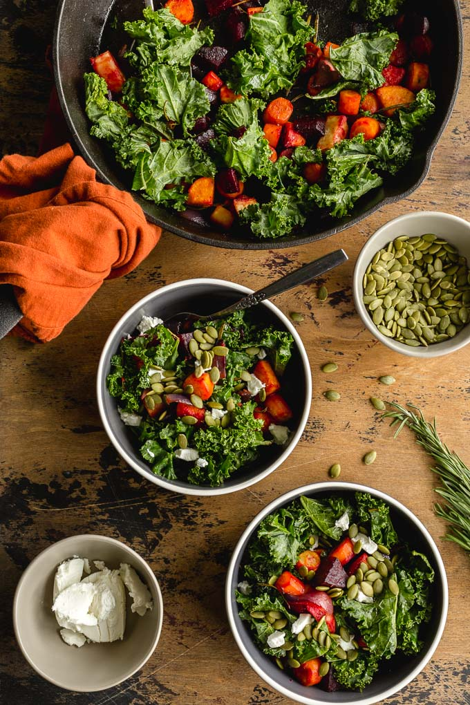 Overhead view of roasted rosemary root vegetables with kale in a skillet and served into two bowls.