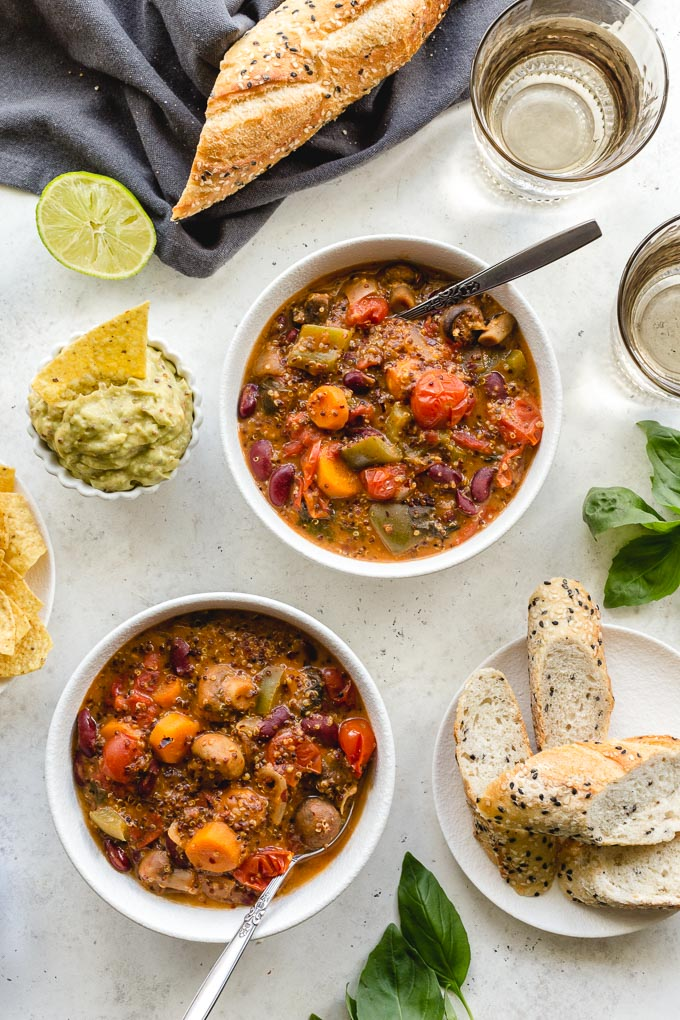 Overhead view of two bowls of chili with bread, chips and guacamole off to the sides.