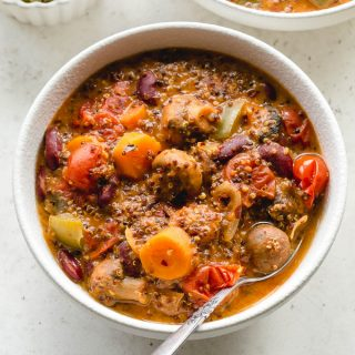 Slow cooker vegetarian chili with quinoa in a white bowl with a spoon.
