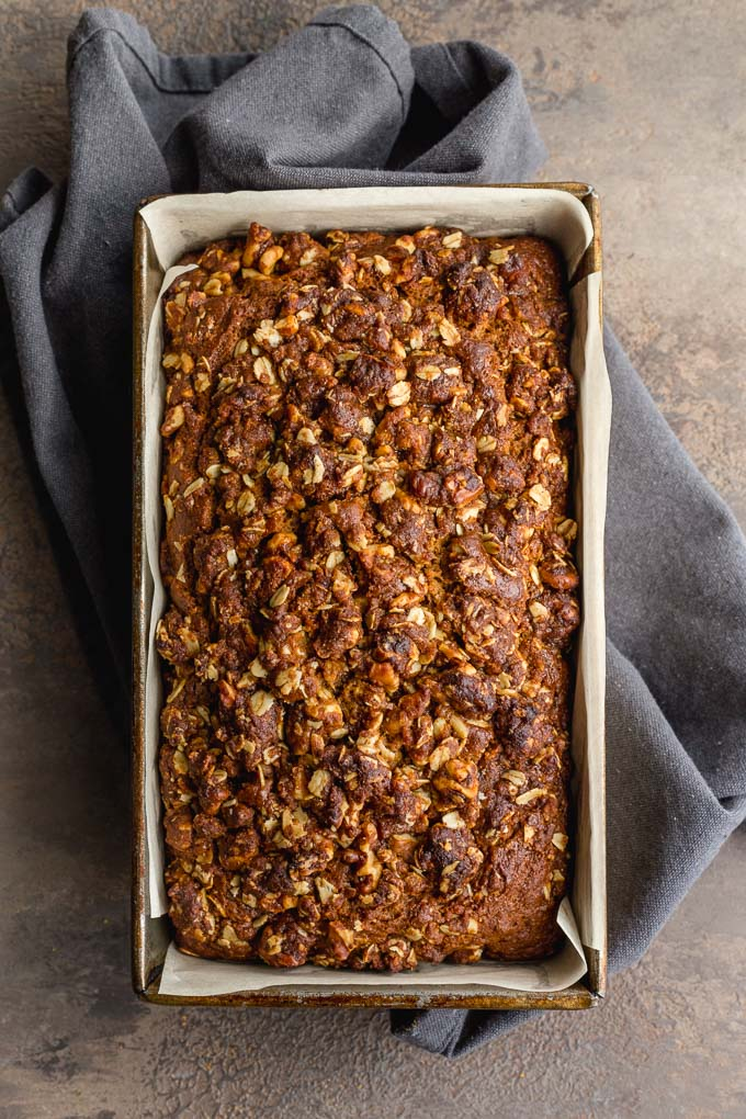 Banana bread with walnuts, molasses and a streusel topping baked up in a loaf pan.