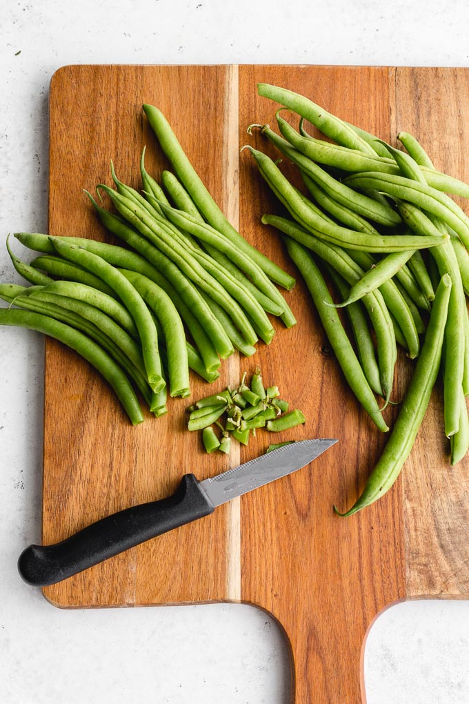 Raw green beans being trimmed on a wooden cutting board.
