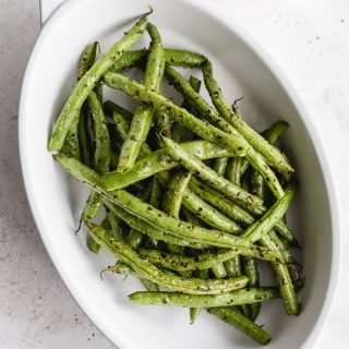 Air Fryer Green Beans served in a white oval dish with lemon wedges off to the side.
